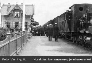 Fra perrongen på Hamar stasjon med ankommende persontog trukket av damplok type VI i spor 1. En gruppe (sangere?) oppstilt for fotografering. 1880-85
