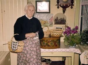 Gunhild Øvergård med tegerarbeider og strikking.